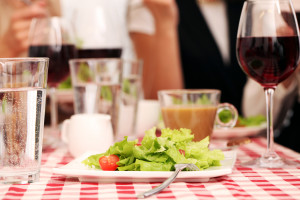 Healthy salad and red wine in a restaurant on a squared tableclo